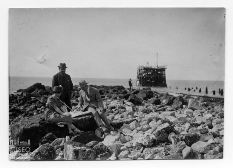 Enrico Tiraboschi con una donna e un uomo su una spiaggia di rocce osservano una mappa di navigazione