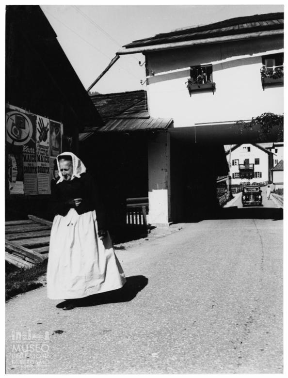 Donna anziana in costume tradizionale in un paese di montagna