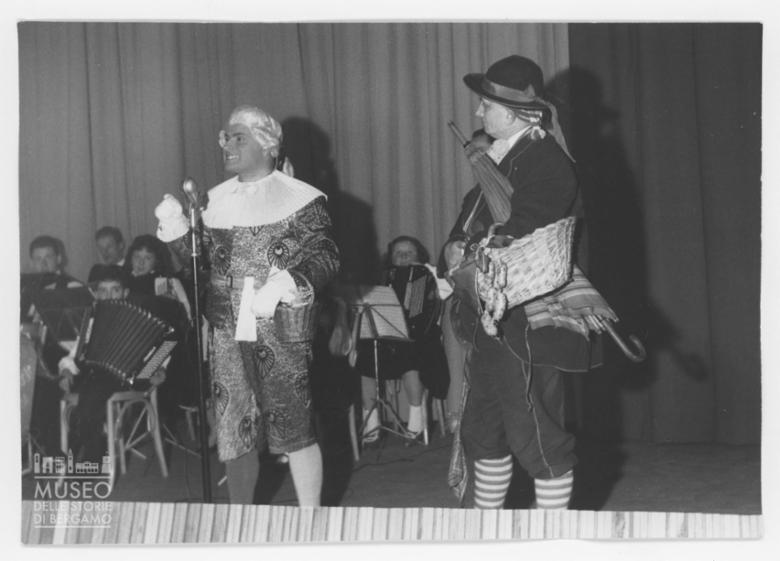 Due uomini in maschera sul palco di un teatro