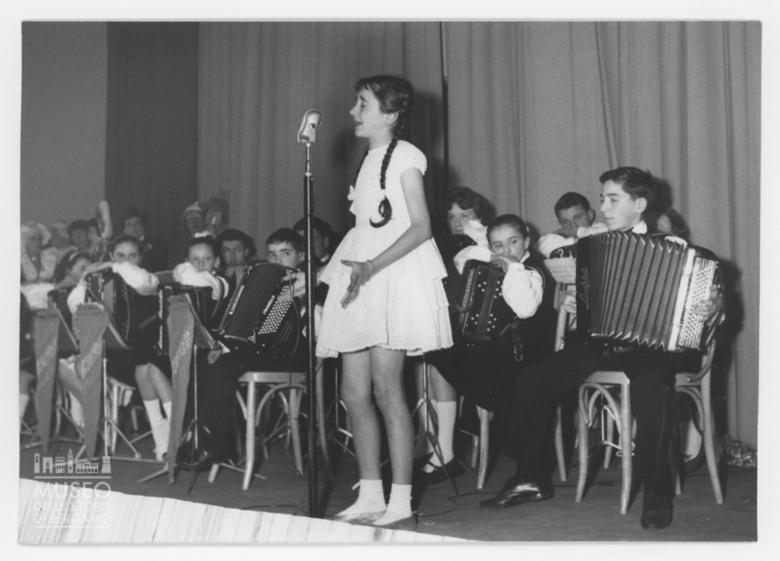 Una bambina canta sul palco di un teatro
